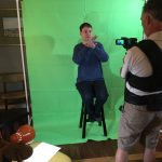 Ryan sitting on a stool in front of green screen while Wes films with camera.