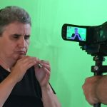 Close-up headshot of Rita being filmed in front of the green screen.